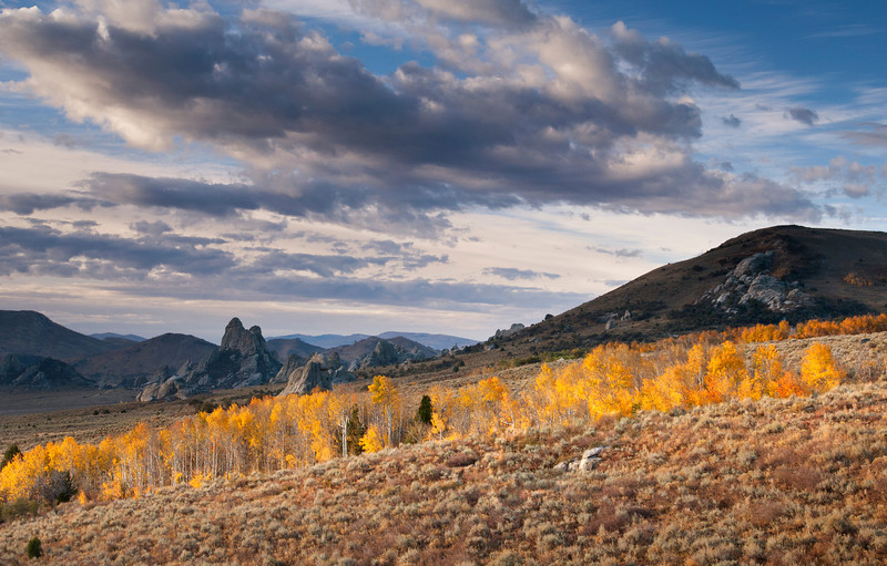 October Morning, City of Rocks - Idaho  Early light paints the aspen groves with brilliant color, as rain clouds drift toward the horizon - over the twin summits of the Twin Sisters. For many years, pioneer wagon trains followed the meandering ruts of the California Trail, through the towering rock spires of the City of Rocks, in route to the mythical goldfields that awaited them along the Pacific coast.