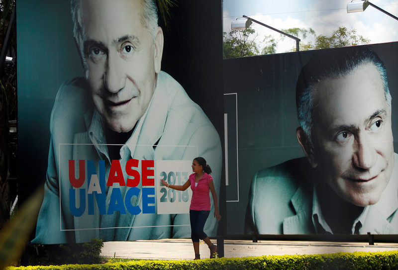 . A woman touches a campaign poster of presidential candidate former Gen. Lino Cesar Oviedo outside the UNACE (National Union of Ethical Citizens) party headquarters in Asuncion, Paraguay,  Sunday,  Feb. 3, 2013.  Oviedo was killed in a helicopter crash Saturday night, authorities said Sunday, ending a dramatic political career that included coups and repeated attempts to lead Paraguay. (AP Photo/Jorge Saenz)