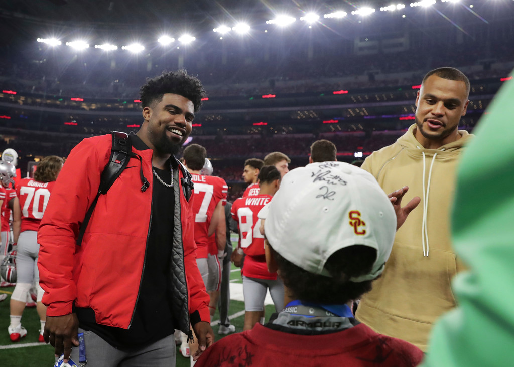 . Dallas Cowboys running back Ezekiel Elliott, left, and quarterback Dak Prescott visit with fans during the first half of the Cotton Bowl NCAA college football game between Ohio State and Southern California in Arlington, Texas, Friday, Dec. 29, 2017. (AP Photo/LM Otero)