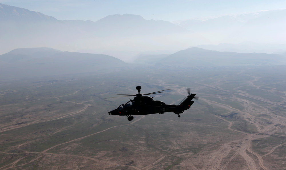 Description of . A German Bundeswehr armed forces Tiger attack helicopter flies next to the Marmal mountain near Camp Marmal in Mazar-e-Sharif, northern Afghanistan December 20, 2012.    REUTERS/Fabrizio Bensch