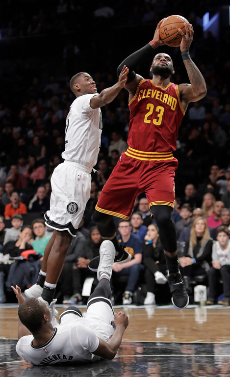 . Cleveland Cavaliers\' LeBron James (23) shoots over Brooklyn Nets\' Caris LeVert, left, and Isaiah Whitehead, below, during the first half of an NBA basketball game Friday, Jan. 6, 2017, in New York. (AP Photo/Frank Franklin II)