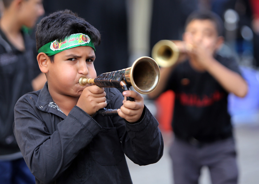 . Iraqi Shiite boys play horns during a parade in preparation for the peak of the mourning period of Ashura in Baghdad\'s northern district of Kadhimiya on November 1, 2014.  AHMAD AL-RUBAYE/AFP/Getty Images