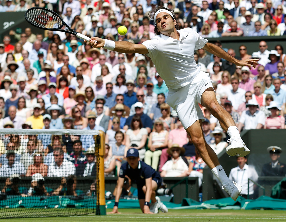. Roger Federer of Switzerland leaps in an attempt to play a return to Novak Djokovic of Serbia during their men\'s singles final match at the All England Lawn Tennis Championships in Wimbledon, London, Sunday, July 6, 2014. (AP Photo/Sang Tan, Pool)