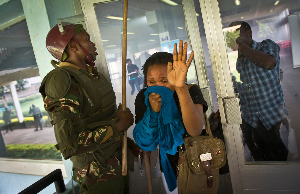 . A student or member of university staff overcome by tear gas holds a cloth to her face and puts her hands in the air as she tries to escape from a tear-gas-filled building inside Nairobi University\'s main campus in downtown Nairobi, Kenya Tuesday, May 20, 2014. Kenyan university students on Tuesday carried out demonstrations over a proposed increase in student fees, but the protests quickly turned into hours of running battles between students throwing rocks and security forces firing tear gas, before riot police chased the students inside their campus and cornered them in a building into which they fired dozens of tear gas grenades and for a while prevented anyone from leaving. (AP Photo/Ben Curtis)