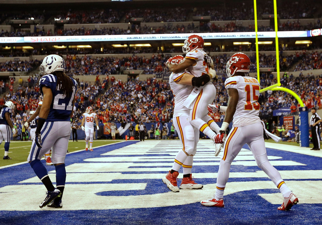 . After scoring a 10-yard touchdown reception, Kansas City Chiefs running back Knile Davis (34) jumps into the arms of Geoff Schwartz (74) as wide receiver A.J. Jenkins (15) moves in during the second half of an NFL wild-card playoff football game Saturday, Jan. 4, 2014, in Indianapolis. Colts defensive back Josh Gordy (27) walks away. (AP Photo/AJ Mast)