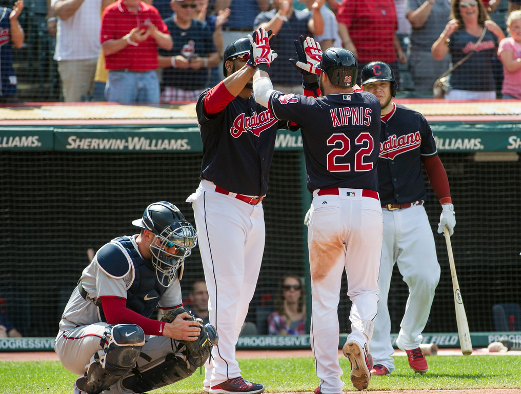 . Cleveland Indians\' Jason Kipnis (22) is greeted by Edwin Encarnacion and Roberto Perez after hitting a three-run home run as Minnesota Twins\' Mitch Garver looks away during the sixth inning of a baseball game in Cleveland, Thursday, Aug. 30, 2018. (AP Photo/Phil Long)