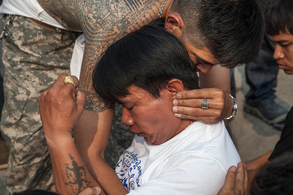 . A Thai devotee in state of trance is helped by a volunteer during the celebration of the annual Tattoo festival at Wat Bang Phra on March 15, 2014 in Nakhon Pathom, Thailand.  T(Photo by Omar Havana/Getty Images)