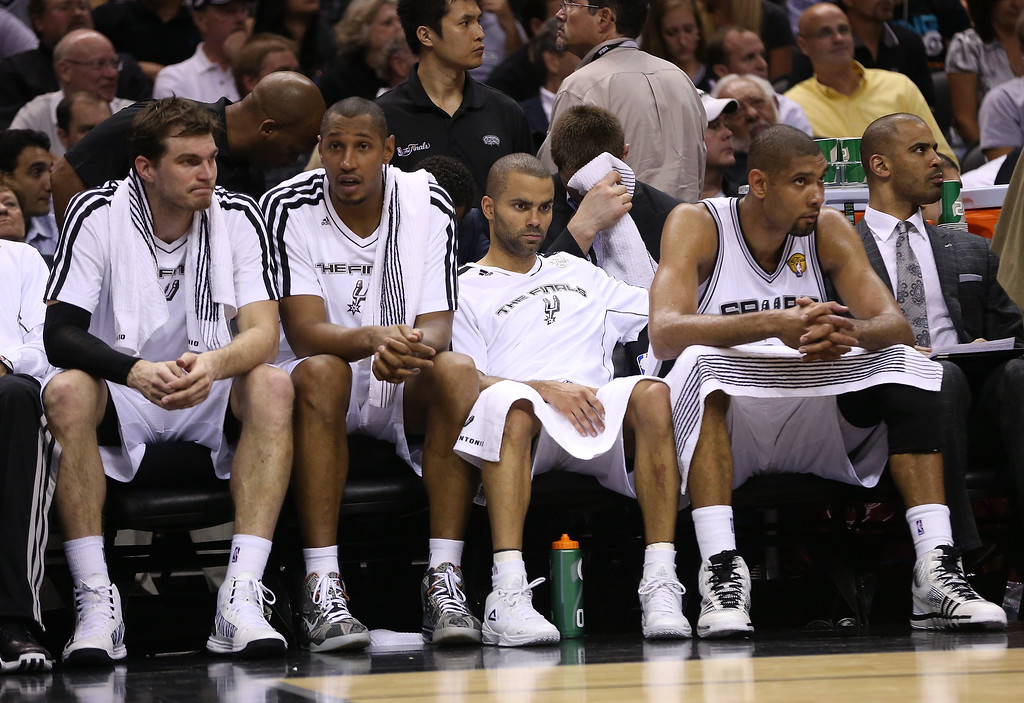 . Tiago Splitter #22, Boris Diaw #33, Tony Parker #9 and Tim Duncan #21 of the San Antonio Spurs sit on the bench late in the fourth quarter while taking on the Miami Heat during Game Four of the 2013 NBA Finals at the AT&T Center on June 13, 2013 in San Antonio, Texas.  (Photo by Christian Petersen/Getty Images)