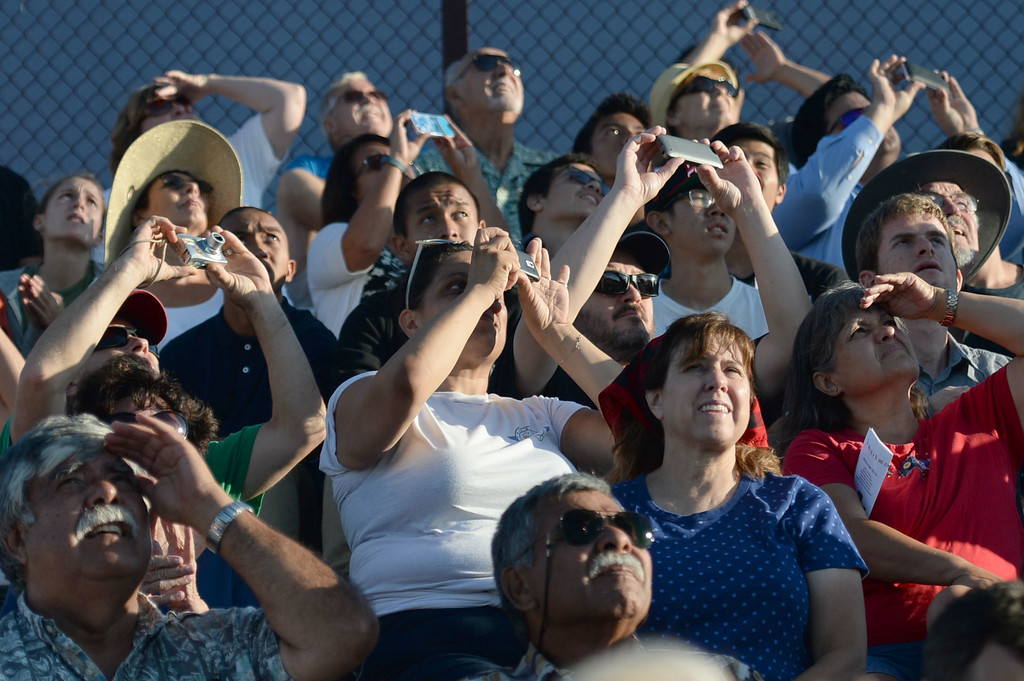 . People watch and photograph a fly-over during a memorial for Torrance legend Louis Zamperini who died earlier this month Thursday, July 31, 2014, Torrance, CA.  Zamperini was an Olympian, WWII bomber pilot and Japanese POW. A book by Laura Hildebrand titled Unbroken documented his life and a movie directed by Angelina Jolie will be released in December. Photo by Steve McCrank/Daily Breeze