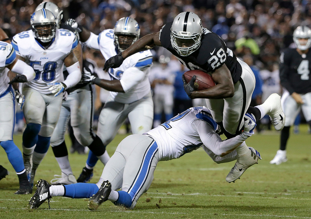 . Oakland Raiders running back Latavius Murray (28) is tackled by Detroit Lions free safety Isa Abdul-Quddus (42) an NFL preseason football game in Oakland, Calif., Friday, Aug. 15, 2014. (AP Photo/Marcio Jose Sanchez)