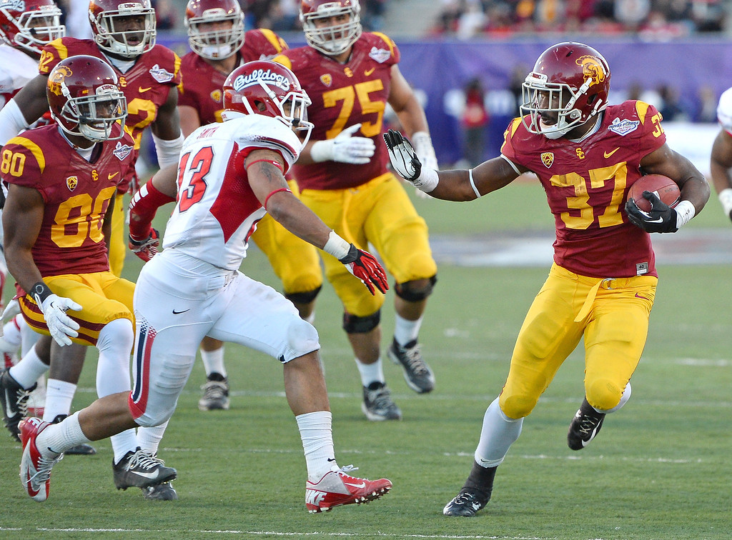 . LAS VEGAS, NV - DECEMBER 21:  Javorius Allen #37 of the USC Trojans tries to get away from Derron Smith #13 of the Fresno State Bulldogs during the Royal Purple Las Vegas Bowl at Sam Boyd Stadium on December 21, 2013 in Las Vegas, Nevada. USC won 45-20.  (Photo by Ethan Miller/Getty Images)