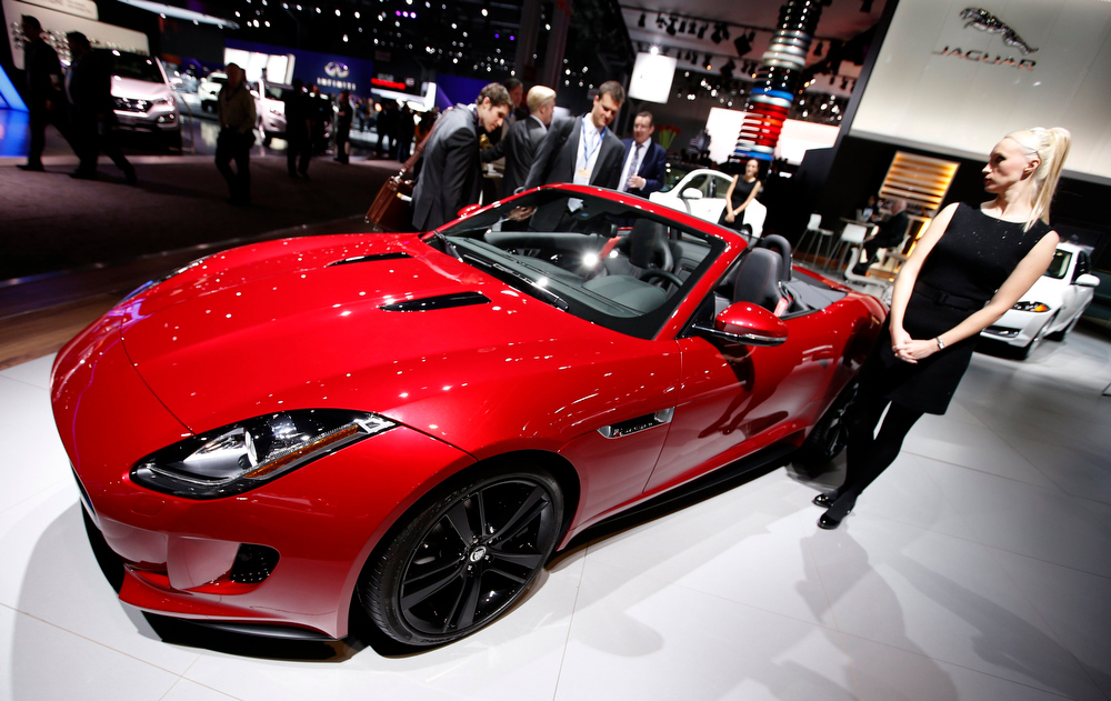 Description of . A model stands next to a Jaguar F Type S convertible model, winner of the 2013 World Car Awards World Car Design of the Year during a press preview at the 2013 New York International Auto Show in New York, March 28, 2013.   REUTERS/Mike Segar