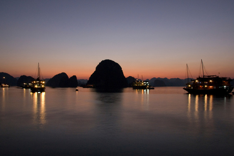 Wide shot of boats and islands during sunset in Ha Long Bay, Vietnam