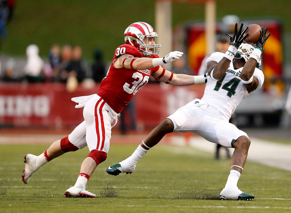 . Michigan State wide receiver Tony Lippett (14) hauls in a pass against Indiana  safety Chase Dutra (30) during an NCAA college football game in Bloomington, Ind., Saturday, Oct. 18, 2014. Michigan State won the game 56-17. (AP Photo/Sam Riche)