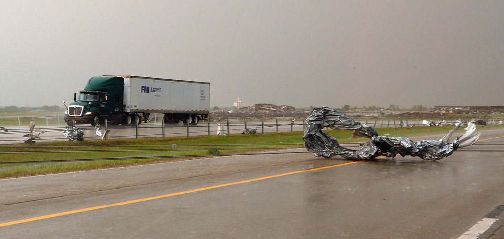 . Tornado debris and downed power lines are seen at Interstate-40 Westbound as traffic slowly passes in the opposite direction of Interstate-40, just east of El Reno, Oklahoma May 31, 2013. Violent thunderstorms spawned tornadoes that menaced Oklahoma City and its already hard-hit suburb of Moore on Friday, killing a mother and her baby, and officials worried that drivers stuck on freeways could be trapped in the path of dangerous twisters. One twister touched down on Interstate 40 and was headed toward Oklahoma City.  REUTERS/Bill Waugh