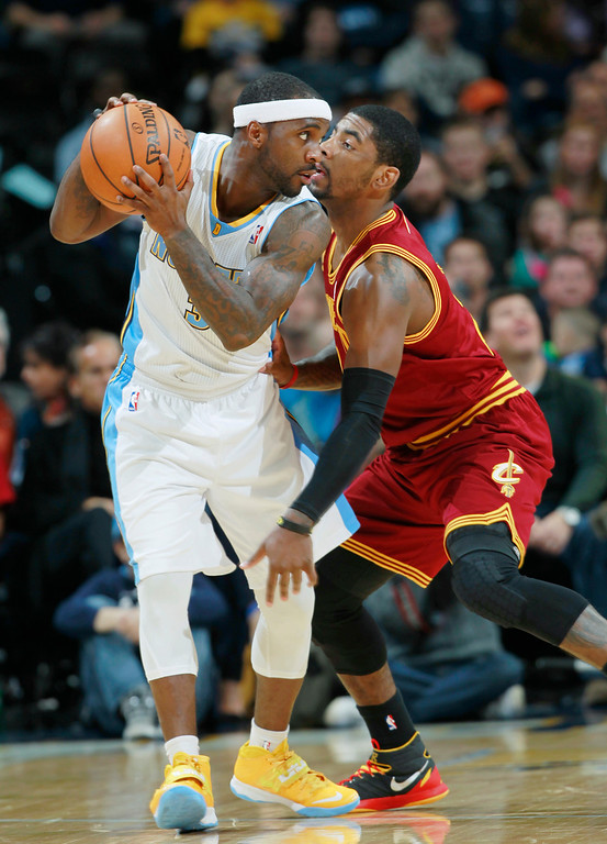. Denver Nuggets guard Ty Lawson, left, looks to pass ball as Cleveland Cavaliers guard Kyrie Irving covers in the first quarter of an NBA basketball game in Denver on Friday, Jan. 17, 2014. (AP Photo/David Zalubowski)