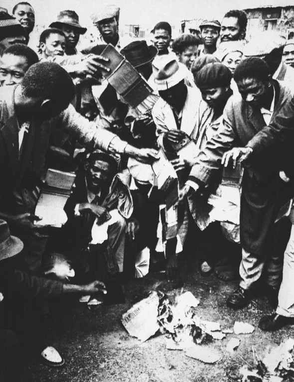 ". South African blacks burn government passes no longer required by them as new violence among the black population erupted at Orlando, near Johannesburg, South Africa, March 28, 1960. In violence centered around Johannesburg and Cape Town, police and Africans mixed when some blacks fought others of their race who insisted on going to work in defiance of a ""Day of Mourning\"" for those killed by white police just a week ago. (AP Photo/Dennis Lee Royle)"