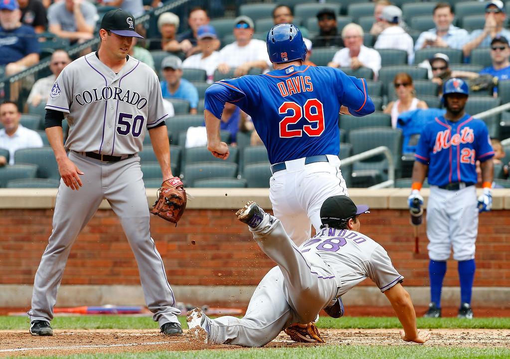 . Jeff Manship #50 of the Colorado Rockies watches teammate Nolan Arenado #28 tag out Ike Davis #29 of the New York Mets at home plate for the final out of the fourth inning at Citi Field on August 8, 2013 in the Flushing neighborhood of the Queens borough of New York City. The Mets defeated the Rockies 2-1.  (Photo by Jim McIsaac/Getty Images)