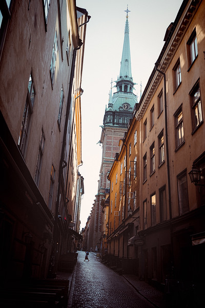 A woman walks through the street below the  German church in Stockholm.