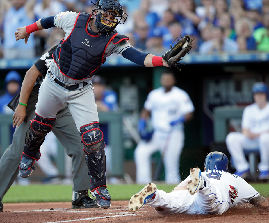 . Kansas City Royals\' Mike Moustakas (8) slides under the tag of Cleveland Indians catcher Yan Gomes, left, during the first inning of a baseball game at Kauffman Stadium in Kansas City, Mo., Monday, July 2, 2018. Moustakas scored on a single by teammate Salvador Perez. (AP Photo/Orlin Wagner)