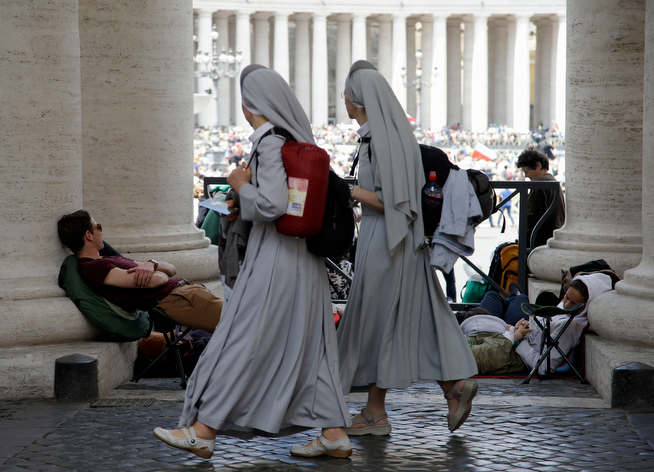 . Nuns walks past pilgrims in St. Peter\'s Square at the Vatican, Saturday, April 26, 2014. Pilgrims and faithful are gathering at the Vatican ahead of Sunday\'s ceremony in which Pope Francis will elevate John XXIII and John Paul II to sainthood. (AP Photo/Gregorio Borgia)