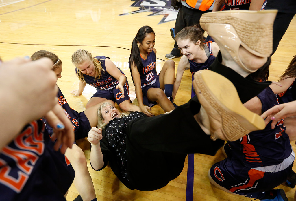 . Chaminade head coach Kelli DiMuro lands on her back after she was dragged into a celebration pile after defeating Archbishop Mitty 80-51 in the girls\' Division 2 CIF basketball championship game Saturday, March 29, 2014, in Sacramento, Calif.(AP Photo/Rich Pedroncelli)