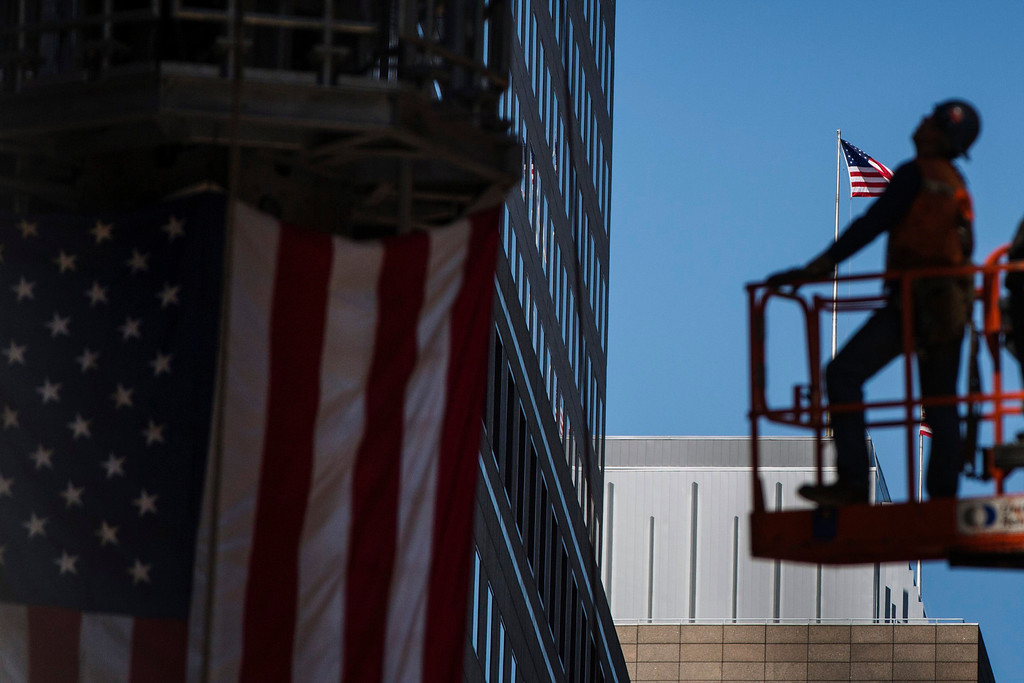 . A U.S. flag flies on a building behind workers from the Ground Zero site as they prepare the final piece of One World Trade Center\'s spire to be lifted to the top of the building, in New York May 2, 2013. REUTERS/Lucas Jackson