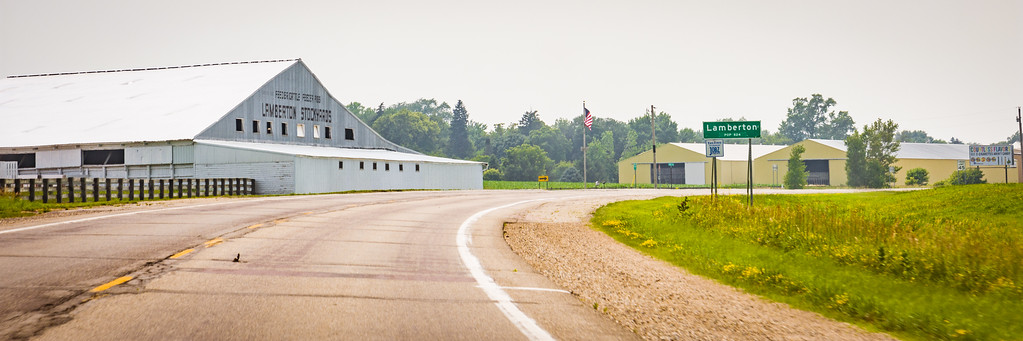 A highway curves past a sign that says 'Lamberton' and a very large barn that has 'Lamberton Stockyards' painted in large lettering across the top.