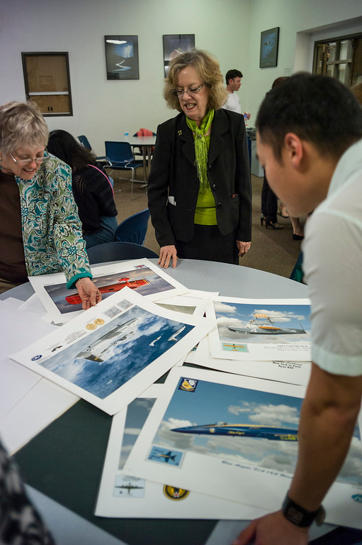 . Valley College president Dr. Susan Carleo, center, look over the artwork of LA Valley College\'s first student, Lloyd Jones, Jones, a world renowned aviation artist was invited back to campus for a Deans reception.  Photo by David Crane/Los Angeles Daily News.