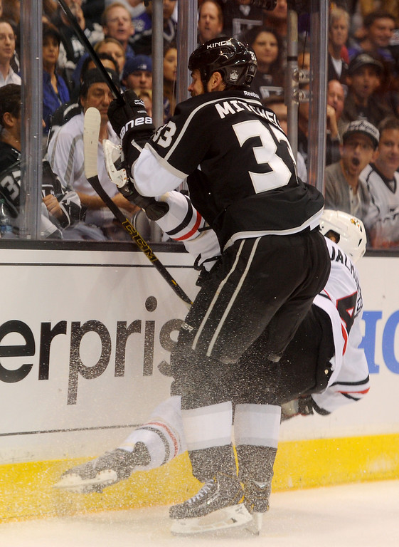. The Kings\' Willie Mitchell checks the Blackhawks\' Niklas Hjalmarsson during game six of the Western Conference Finals, Friday, May 30, 2014, at Staples Center. (Photo by Michael Owen Baker/Los Angeles Daily News)