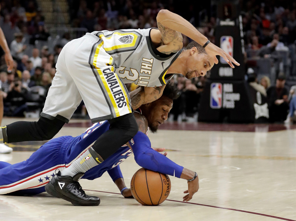 . Cleveland Cavaliers\' George Hill, top, and Philadelphia 76ers\' Robert Covington battle for the ball in the first half of an NBA basketball game, Thursday, March 1, 2018, in Cleveland. (AP Photo/Tony Dejak)
