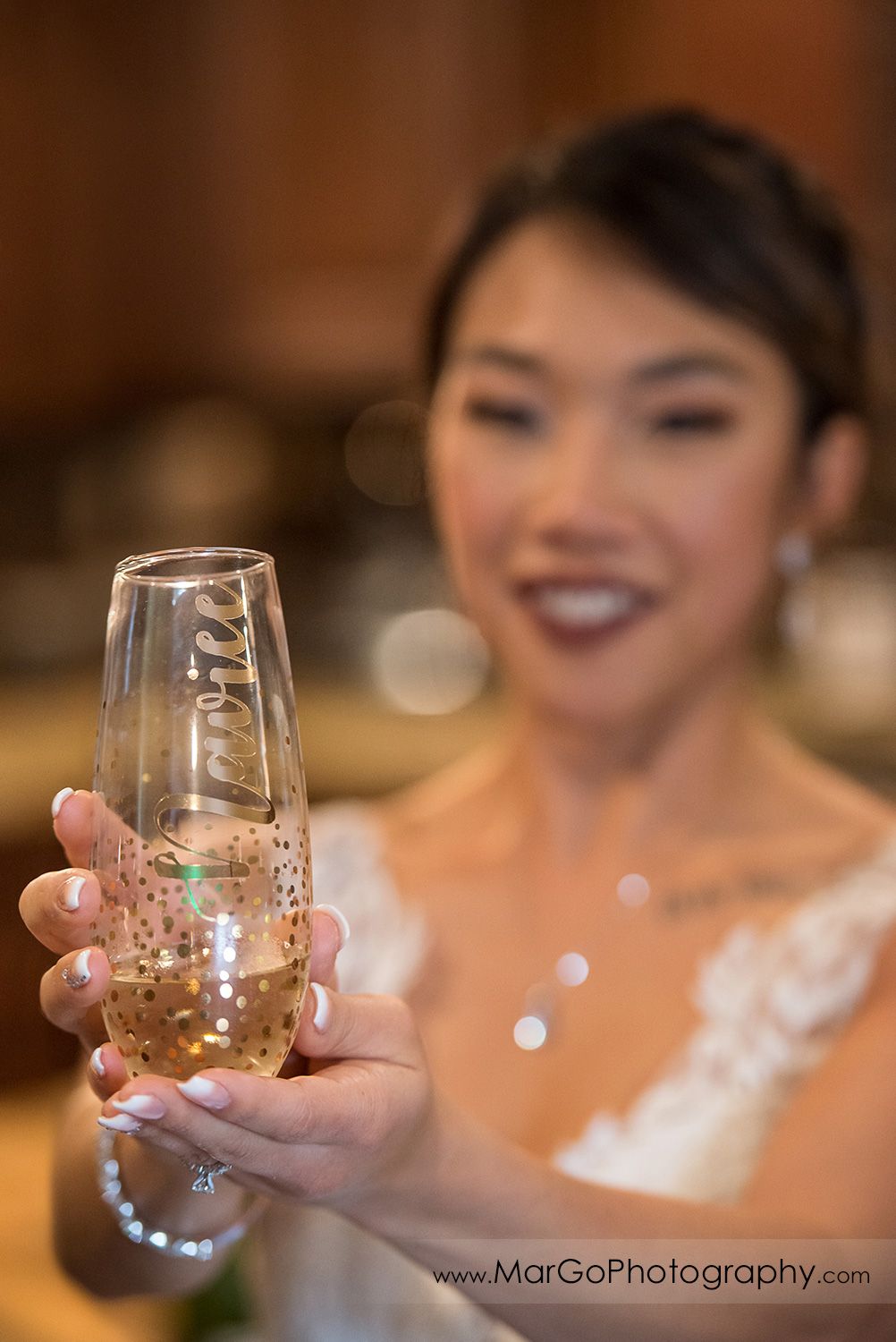 bride showing champagne glass at Sunol's Casa Bella bridal suite