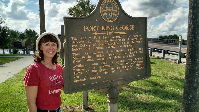 Boomer woman stands in front of historical sign about fort King George in Darien, Georgia.