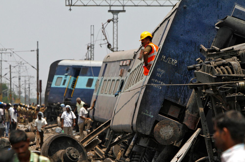 Description of . A rescue worker stands on a derailed coach at the site of a train accident near Arakkonam in the southern Indian state of Tamil Nadu April 10, 2013. One person was killed and dozens were injured after a passenger train derailed in Tamil Nadu, local media reported on Wednesday. REUTERS/Babu