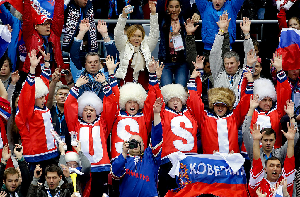 . Russian hockey fans do the wave in the first period of a men\'s ice hockey game between Russia and Slovakia at the 2014 Winter Olympics, Sunday, Feb. 16, 2014, in Sochi, Russia. (AP Photo/Julio Cortez)