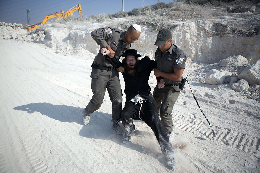 . An Ultra-Orthodox Jewish man is arrested by Israeli  border police during a protest in Ramat Beit Shemesh, west of Jerusalem, on August 14 2013, after dozens of Ultra-Orthodox Jews, known as Haredim, protest for a third day against the desecration of ancient graves which were discovered at a new housing construction site.   MENAHEM KAHANA/AFP/Getty Images