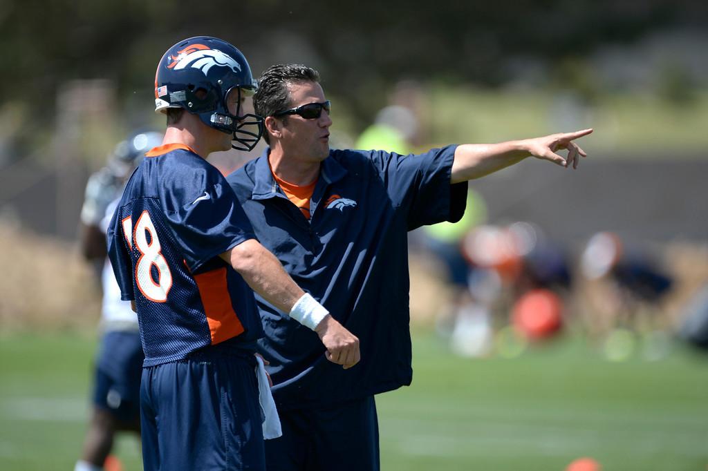 . Denver Broncos Peyton Manning (18) talks with quarterbacks coach Greg Knapp during OTAs June 10, 2014 at Dove Valley. (Photo by John Leyba/The Denver Post)