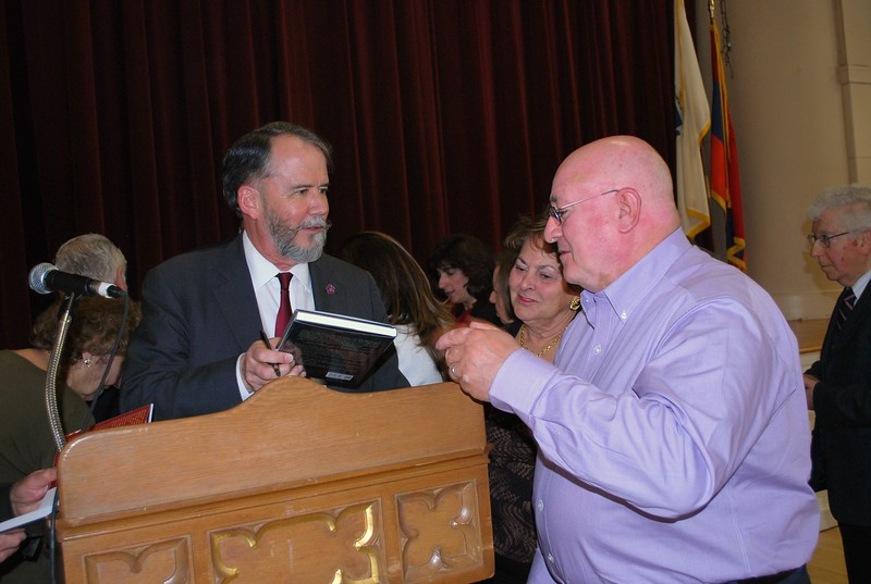 Ambassador Evans signing his book, Truth Held Hostage, for John Hovsepian with Gail O'Reilly looking on.
