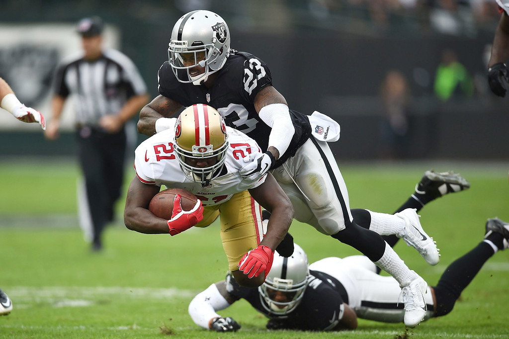 . OAKLAND, CA - DECEMBER 07:  Frank Gore #21 of the San Francisco 49ers catches air from the tackle of Tarell Brown #23 of the Oakland Raiders in the first quarter at O.co Coliseum on December 7, 2014 in Oakland, California.  (Photo by Thearon W. Henderson/Getty Images)