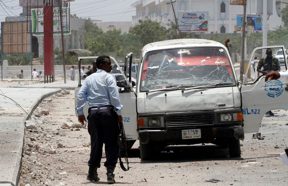 . A policeman stands guard at the scene of an explosion near the presidential palace in Mogadishu March 18, 2013. A car bomb exploded near the presidential palace in the Somali capital Mogadishu on Monday, killing at least 10 people in a blast that appeared to target senior government officials, police said. REUTERS/Feisal Omar