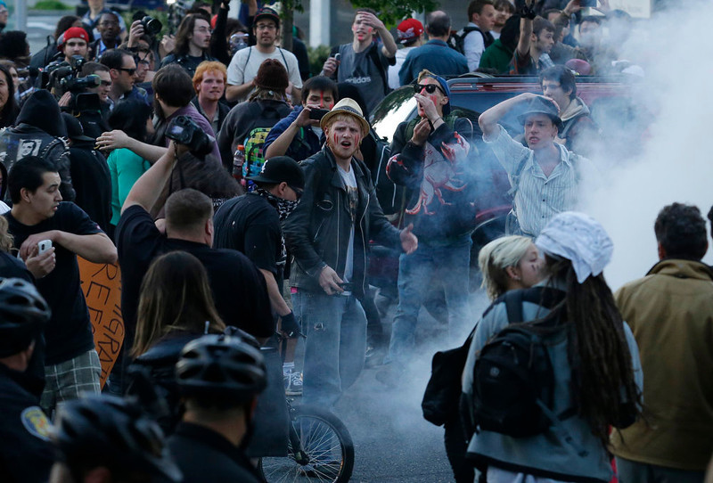 . Protesters, some with painted faces, react as a police flash-bang grenade goes off during a May Day march that began as an anti-capitalism protest and turned into demonstrators clashing with police Wednesday, May 1, 2013, in downtown Seattle. (AP Photo/Ted S. Warren)