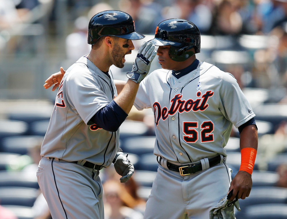 . Detroit Tigers J.D. Martinez, left, celebrates with the Tigers Yoenis Cespedes (52) after hitting a first-inning, two-run, home run off New York Yankees starting pitcher Masahiro Tanaka in a baseball game at Yankee Stadium in New York, Sunday, June 21, 2015.  (AP Photo/Kathy Willens)