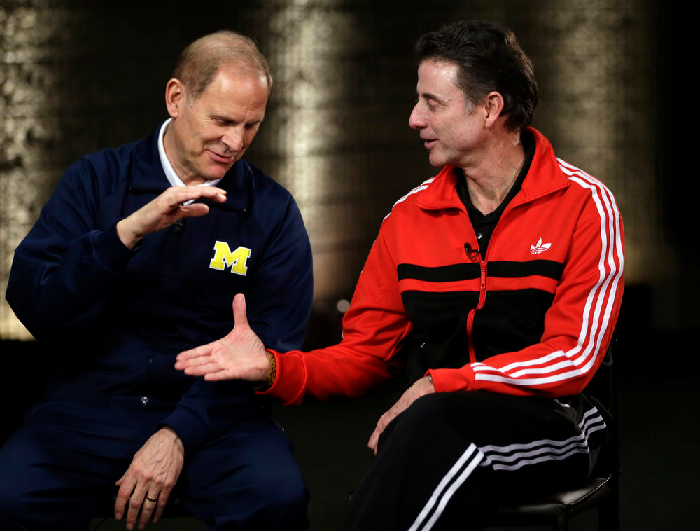 . Louisville head coach Rick Pitino and Michigan head coach John Beilein, left, participate in a television interview for their NCAA Final Four tournament college basketball game Sunday, April 7, 2013, in Atlanta. Louisville plays Michigan in the championship game on Monday. (AP Photo/David J. Phillip)