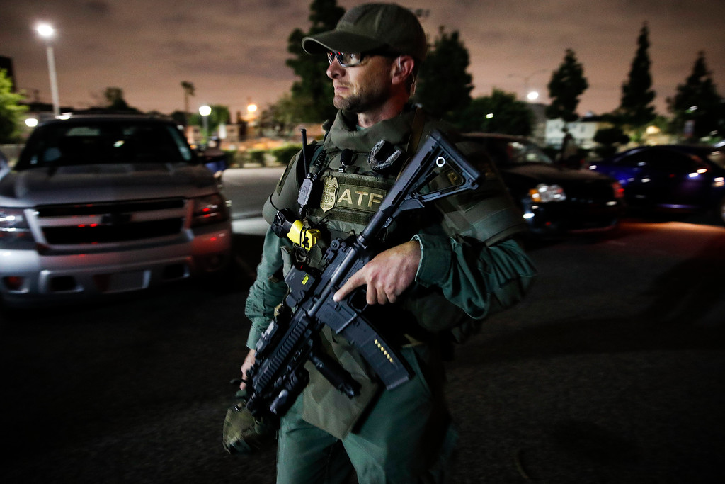 . An ATF agent walks with his rifle while getting ready for a raid early Wednesday morning, May 17, 2017, in Los Angeles. Hundreds of federal and local law enforcement fanned out across Los Angeles, serving arrest and search warrants as part of a three-year investigation into the violent and brutal street gang MS-13. (AP Photo/Jae C. Hong)