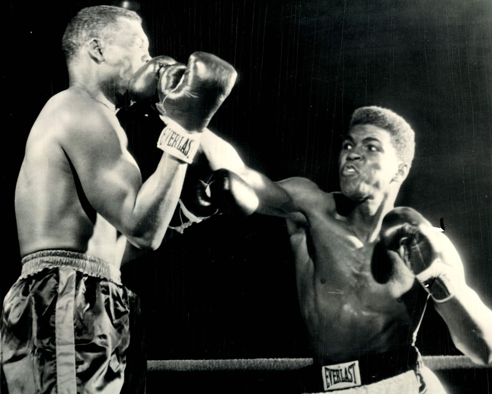 . Cassius Clay (right) lands on Don Warner\'s jaw in an early exchange of their fight tonight with a straight right--the same punch which knocked Warner through the ropes in Round 4 and headed him for a technical knockout as the fight was stopped soon after he climbed back to the canvas. 1962  Credit: AP