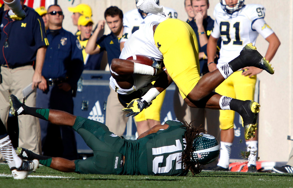 . Michigan receiver Devin Funchess, top, is upended by Michigan State\'s Trae Waynes during the second quarter of an NCAA college football game, Saturday, Oct. 25, 2014, in East Lansing, Mich. (AP Photo/Al Goldis)
