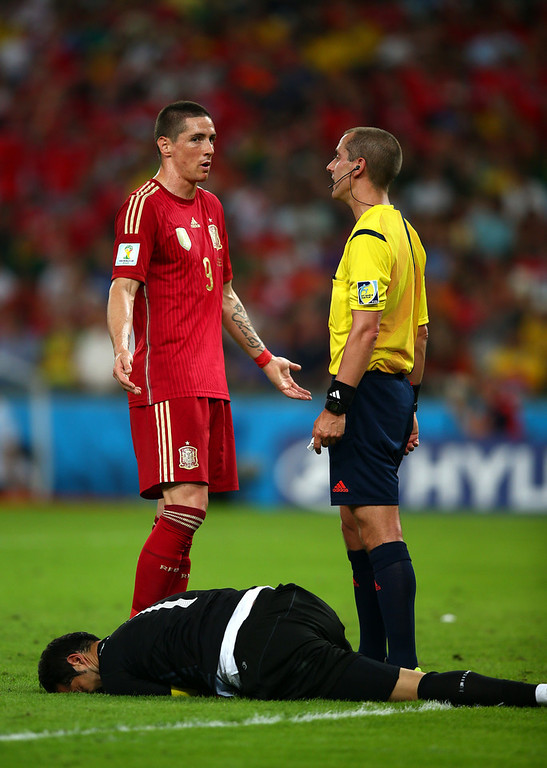 . Referee Mark Geiger speaks to Fernando Torres of Spain as Claudio Bravo of Chile lies on the field during the 2014 FIFA World Cup Brazil Group B match between Spain and Chile at Maracana on June 18, 2014 in Rio de Janeiro, Brazil.  (Photo by Clive Rose/Getty Images)