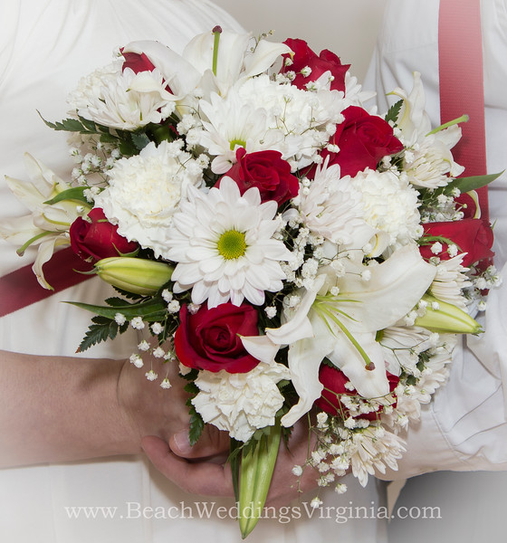 red roses, white lilies, white daisies, carnations, babys breath. Cascading style
