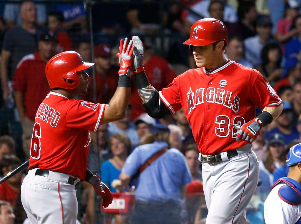 . Los Angeles Angels\' Alberto Callaspo (6) greets Josh Hamilton at home after Hamilton\'s home run off Chicago Cubs starting pitcher Jeff Samardzija during the fifth inning of an interleague baseball game Wednesday, July 10, 2013, in Chicago. (AP Photo/Charles Rex Arbogast)