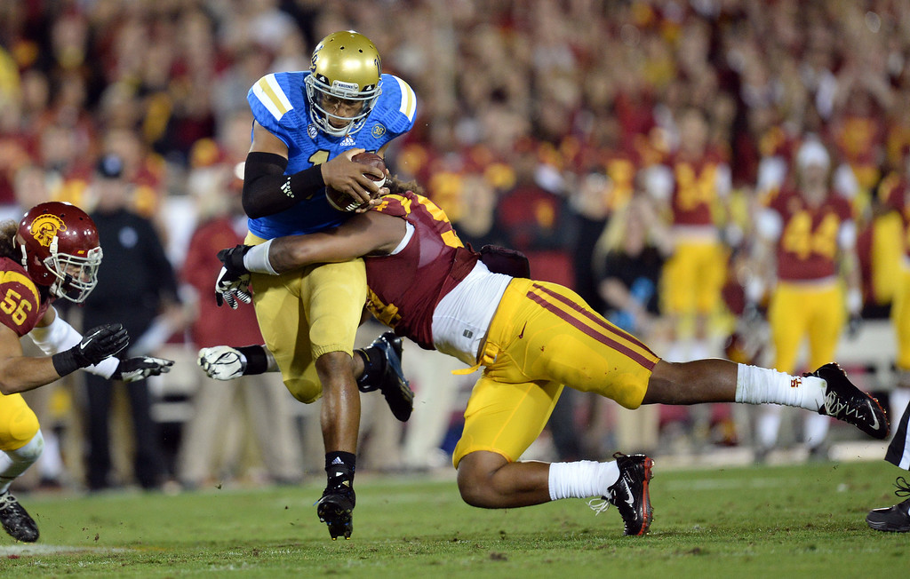 . UCLA�s Brett Hundley #17 scrambles for some yards as USC�s Leonard Williams #94 makes the stop during their game at the Los Angeles Memorial Coliseum Saturday, November 30, 2013.  (Photo by Hans Gutknecht/Los Angeles Daily News)
